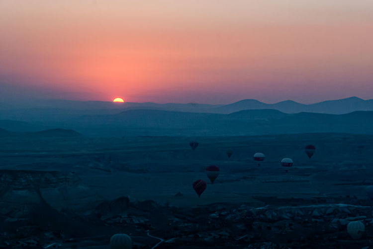 Scenic view of hot air balloons flying over landscape during sunset