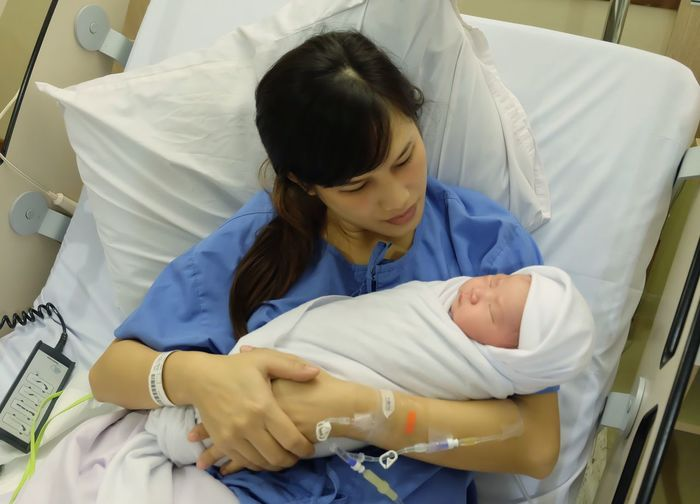 Mother was carrying her newborn baby on bed in the hospital. Eyes Closed  Patient Babyhood People Females Resting Young Baby Indoors  Relaxation Real People High Angle View Healthcare And Medicine Sleeping Lying Down Bed Hospital Child Childhood Furniture Adult Care Indoors  Front View Two People