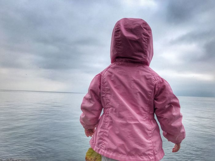 Rear view of baby girl in pink raincoat standing by lake geneva against cloudy sky