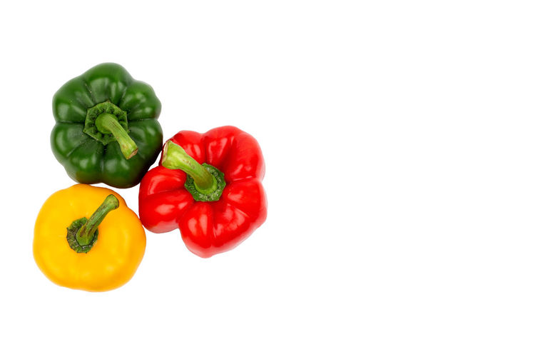 Close-up of red bell peppers against white background