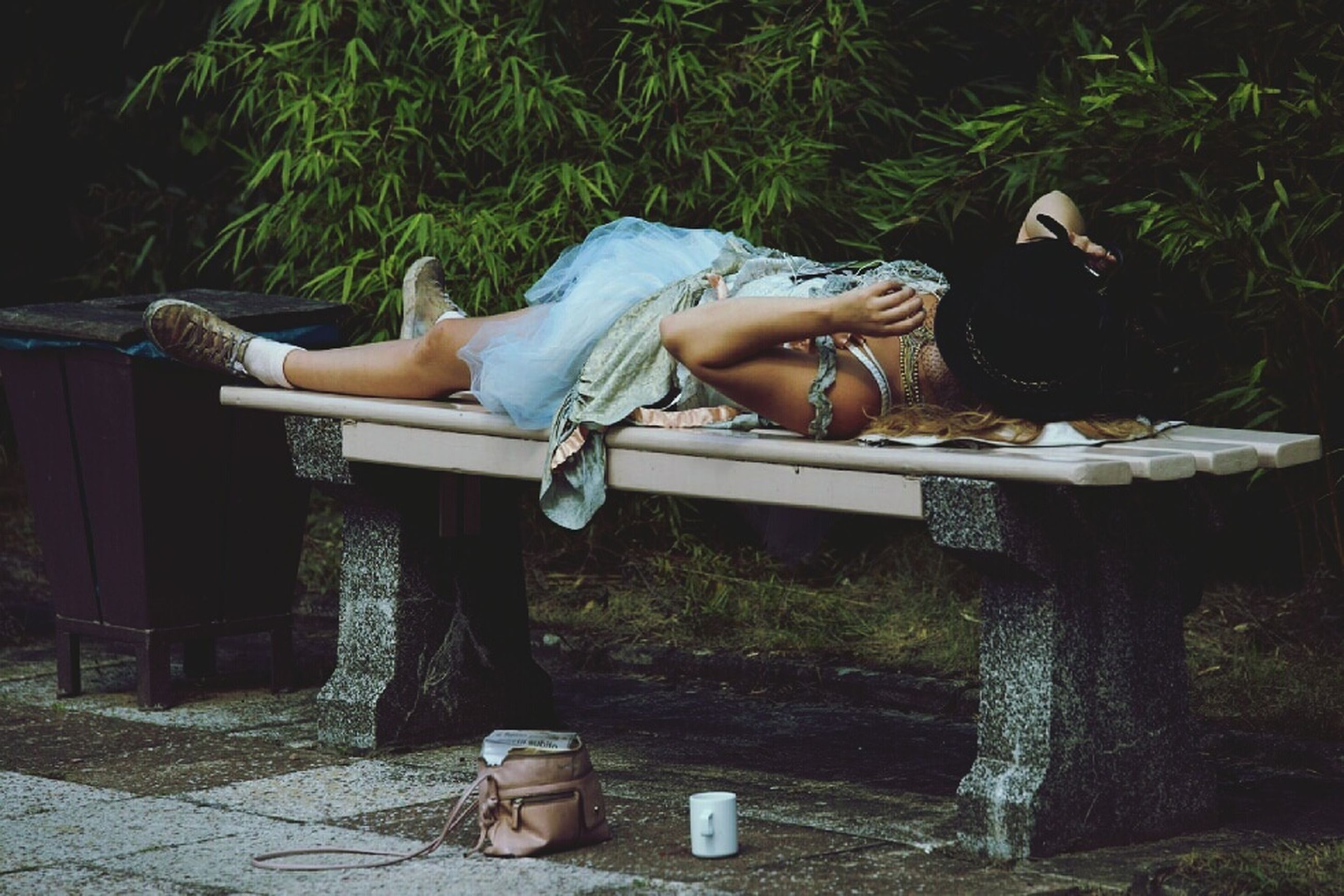 lying down, relaxation, one person, day, plant, lifestyles, real people, full length, men, nature, leisure activity, casual clothing, tree, low section, sleeping, lying on back, outdoors, young adult, bench