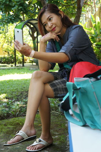 Smiling woman taking selfie while sitting on seat at park