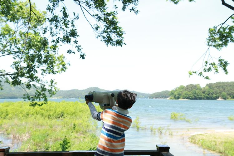 Rear view of boy standing by coin-operated binoculars at observation point against lake