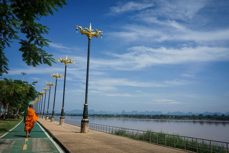 Man by lake against sky