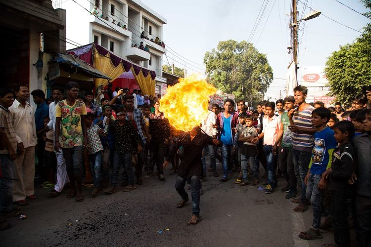 People Looking At Man Performing Fire Stunt On Street