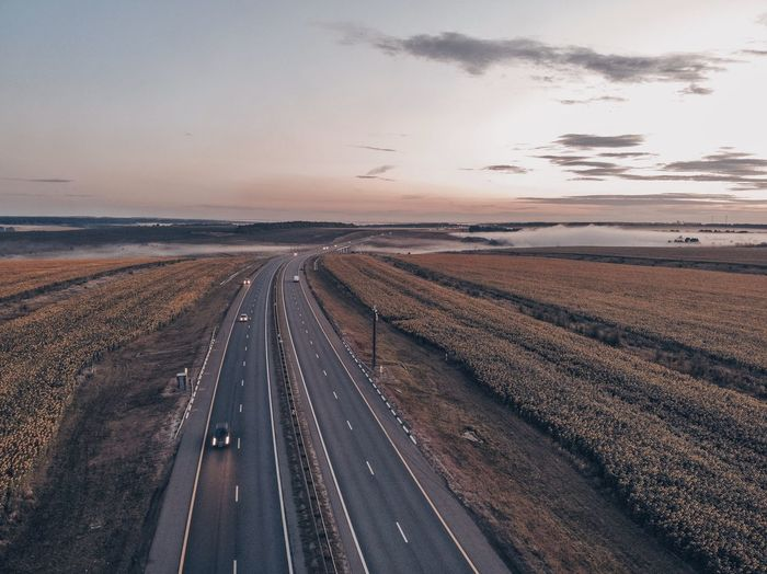 Aerial view of road on land against sky at sunset