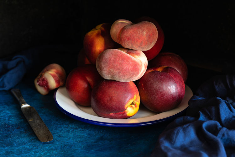 peaches in a metal dish. One of them is cut to show the inside Cut Dessert Green Knife Delicious Food Freshness Fruit Harvest Healthy Eating Ingredient Juicy Fruit No People Nutrients Organic Organic Food Peach Ripe Rustic Style Seasonal Fruit Still Life Sweet Tasty Vitamin Wellbeing