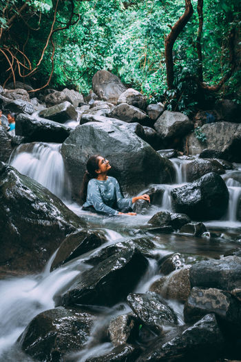 Young woman sitting in stream at forest