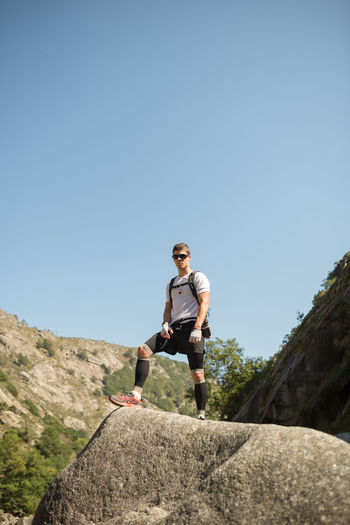 Low angle view of young man on rock against sky