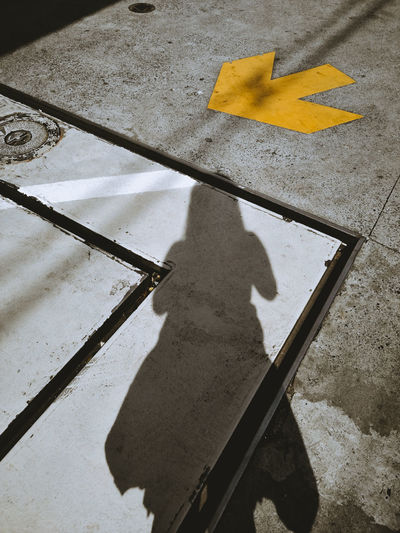 High angle view of yellow shadow on road