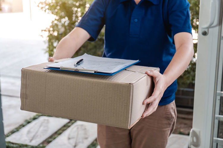 Midsection of man holding camera in box