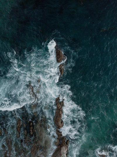 Aerial view of sea waves splashing on rocks