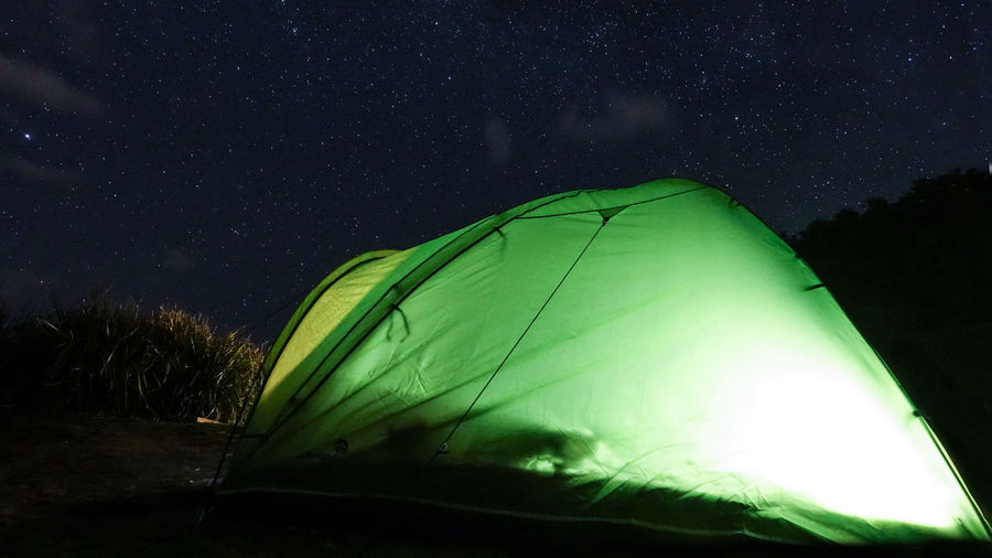 Low angle view of illuminated tent against sky at night
