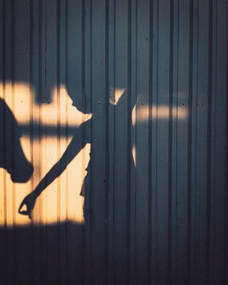 Shadow of girl on corrugated iron