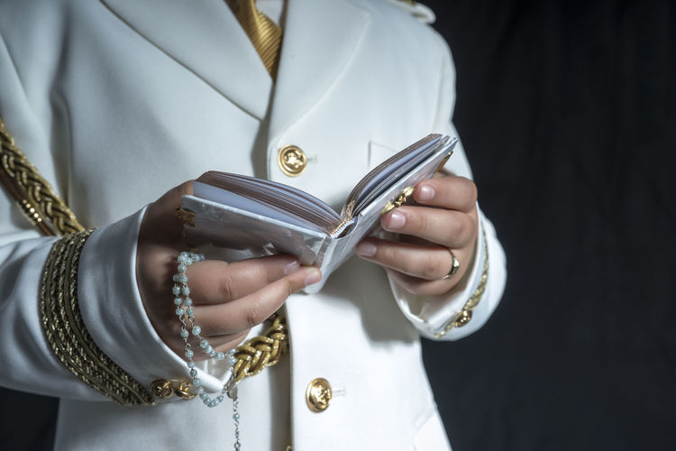 Midsection Of Man Holding Bible Against Black Background