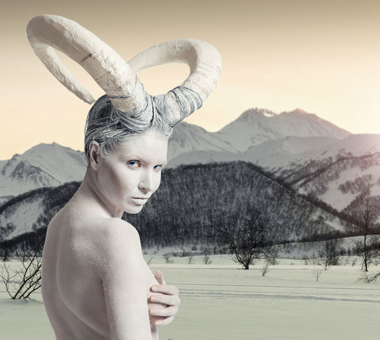 Female with goat body-art over winter countryside background. Dedicated to Chinese Horoscope 2015 - Year of the Goat (Sheep) Model Aries Goat Horns Horoscope  Looking At Camera Makeup New Year RAM Winter Woman Zodiac Sign Astrological Signs Attractive Body Paint Bodyart Calendar Character Conceptual Female Horned Mountain Sheep Snowing Symbol