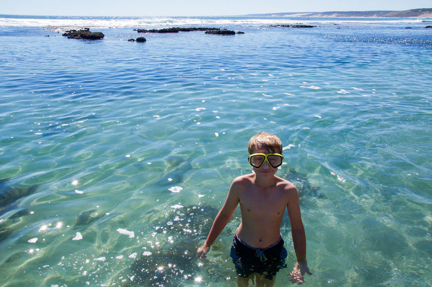 Boy wading and snorkelling in the Indian Ocean rock pools at Blue Holes Beach in Western Australia. Beach Blue Holes Cheerful Child Enjoyment Happiness Indian Ocean Leisure Activity Looking At Camera Nature One Boy Only Outdoors People Sea Smiling Snorkeling Swimming Swimming Goggles Teenager Tourist Travel Destinations Turquoise Vacations Water Western Australia