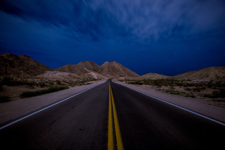 Road amidst landscape against sky at night leading to the mountains