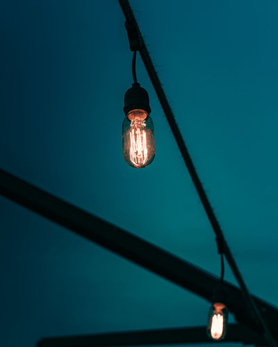 Low angle view of illuminated light bulb against blue sky