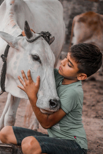 Cute boy embracing with cow outdoors