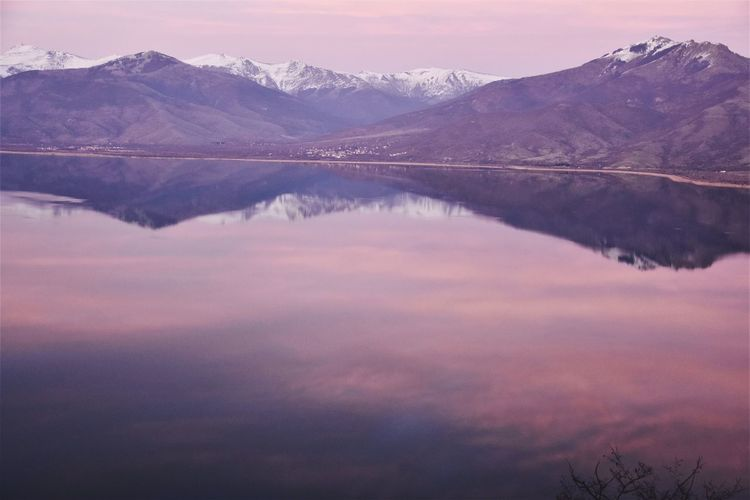 Scenic view of lake and mountains against sky during sunset