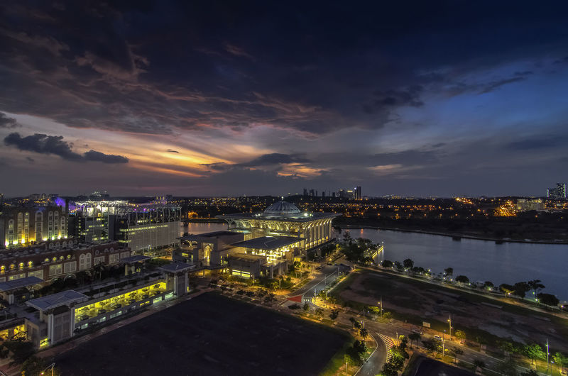 High angle view of illuminated tuanku mizan zainal abidin mosque by river in city against cloudy sky