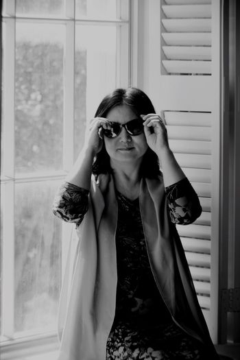 Portrait of woman wearing sunglasses while sitting against window