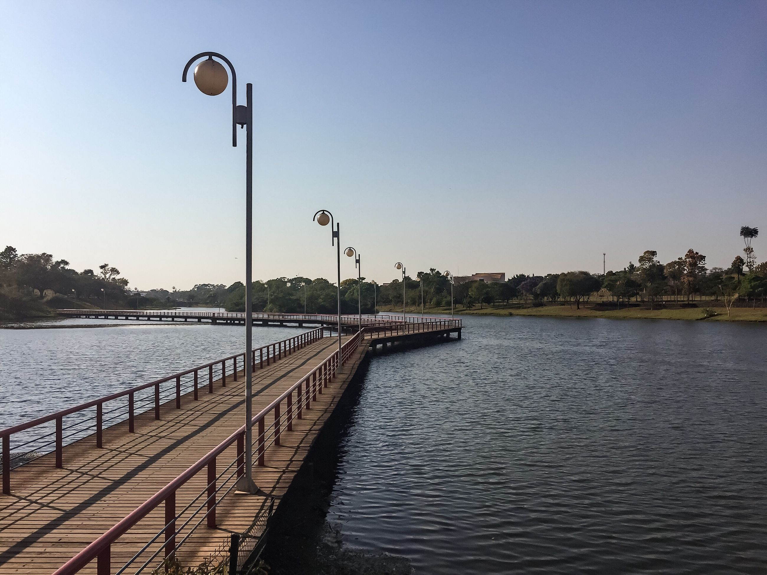 street light, water, clear sky, pier, built structure, the way forward, railing, copy space, diminishing perspective, rippled, in a row, long, walkway, tranquility, tranquil scene, sea, blue, narrow, day, pathway, scenics, nature, mountain, waterfront, railings, vanishing point