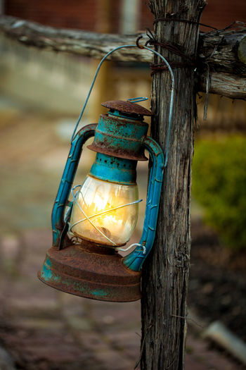 Vintage petrol lantern hanged by fence Antique Rustic Teal Close-up Electricity  Focus On Foreground Hanging Illuminated Lantern Light And Shadow Lighting Equipment No People Oil Lamp Old Outdoors Petrol Portable Information Device Rusty Vintage