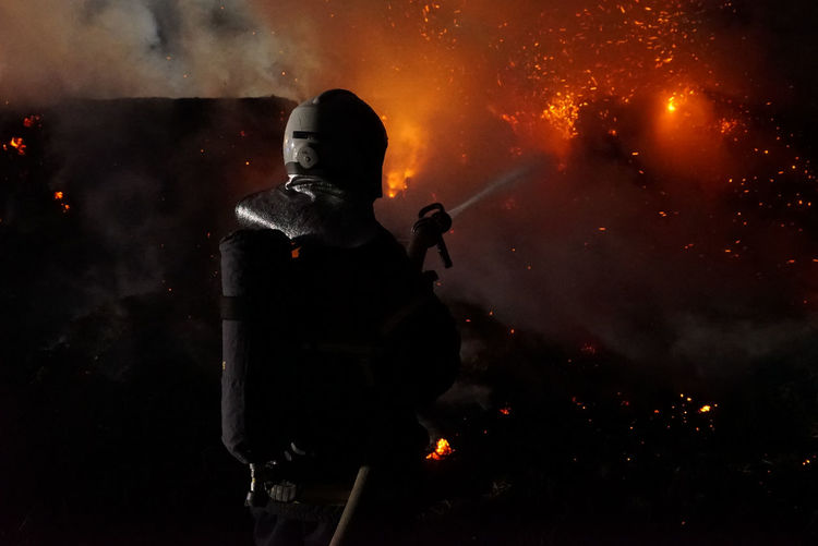 Rear view of firefighter extinguishing fire at night