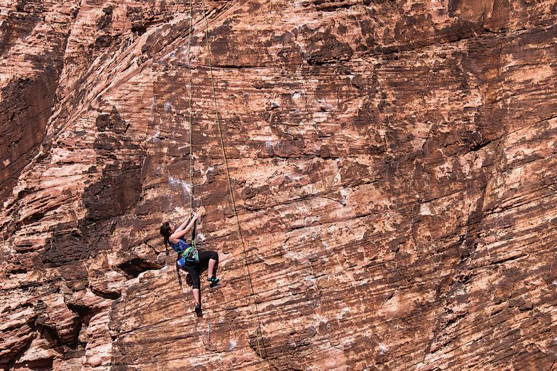 Side View Of Woman Climbing On Rocky Mountain