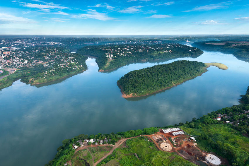 Aerial view of Parana River on the border of Paraguay and Brazil with Ciudad del Este in the back Brazil Ciudad Del Este Paraná River Reflection Aerial View Border Landscape Paraguay River Tropical Vegetation