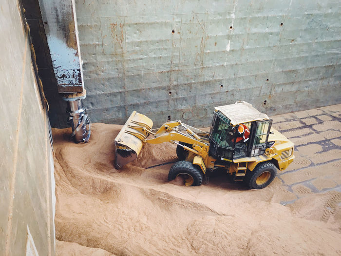 Excavator helping to gather the cereals in a vessel's cargo hold. Animal Feed Cargo Cargo Hold Cargo Ship Cargo Vessel Cereals Excavator Food Food Industry High Angle View Hold Industrial Industry Machinery Nautical Vessel Outdoors Transportation Vessel Vessel Hold