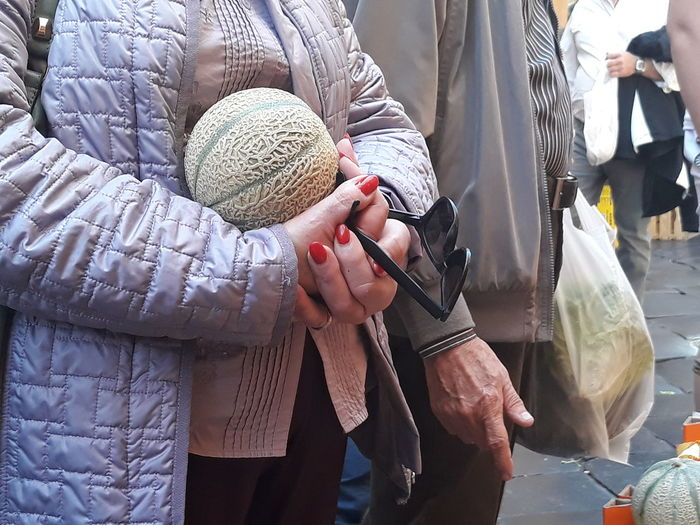 Midsection of woman with cantaloupe standing by man on street market