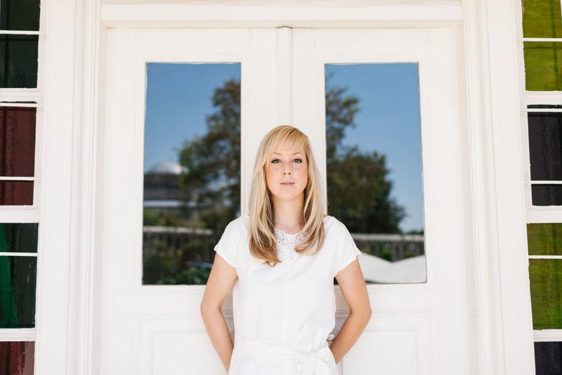 Portrait of beautiful woman standing against closed door