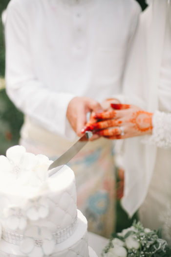 Close-up of couple cutting weeding cake