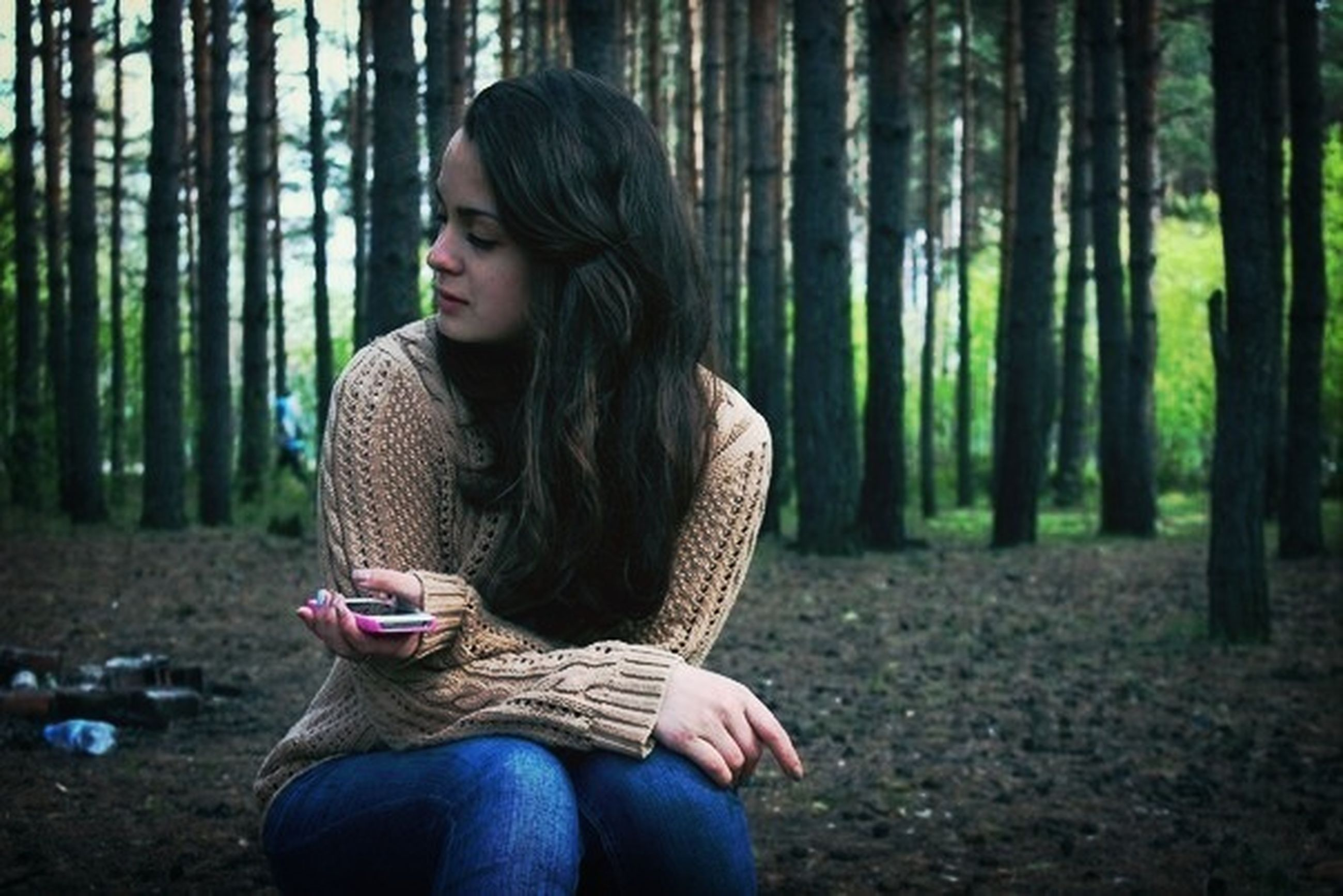 young adult, lifestyles, tree, casual clothing, leisure activity, forest, person, three quarter length, young women, standing, looking at camera, waist up, portrait, sitting, tree trunk, long hair, focus on foreground, front view