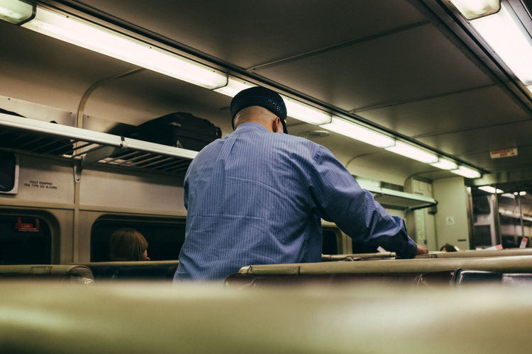 Rear view of man working in train
