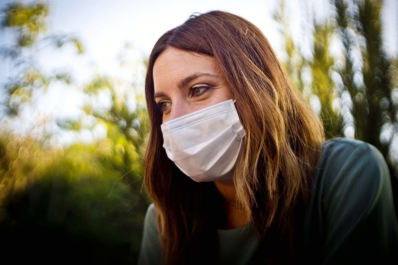 Close-up of woman wearing mask sitting outdoors