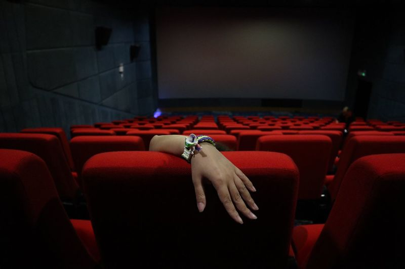 Cropped hand watching movie in theater