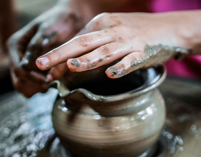 Close-up of hands making pot on pottery wheel
