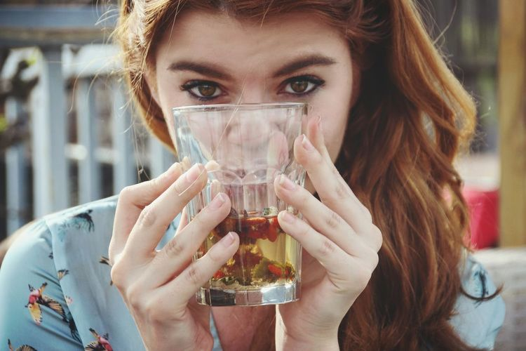 Close-up portrait of a young woman drinking glass