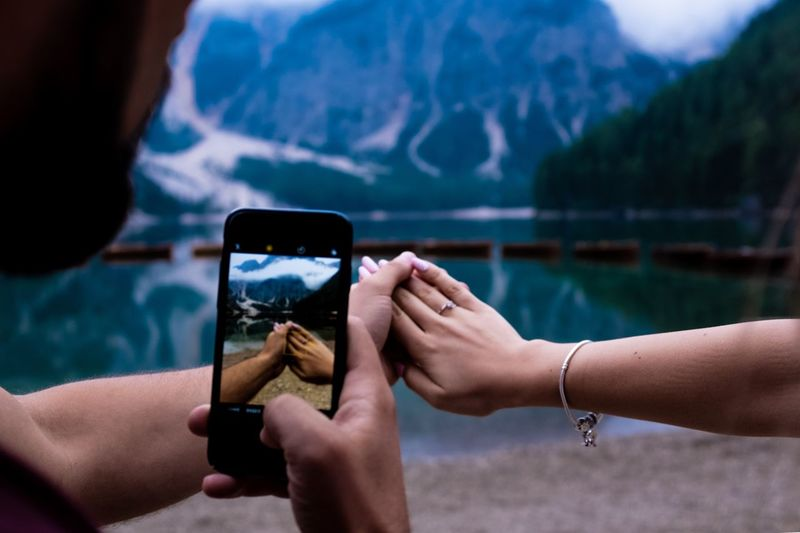 Midsection of man photographing with mobile phone while holding woman hand by lake