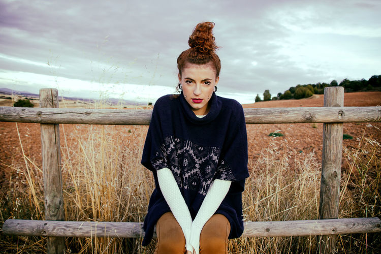Portrait of young woman sitting on railing at field against sky