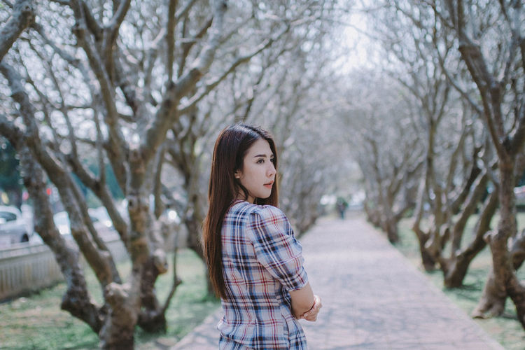 Young woman standing by bare trees in park