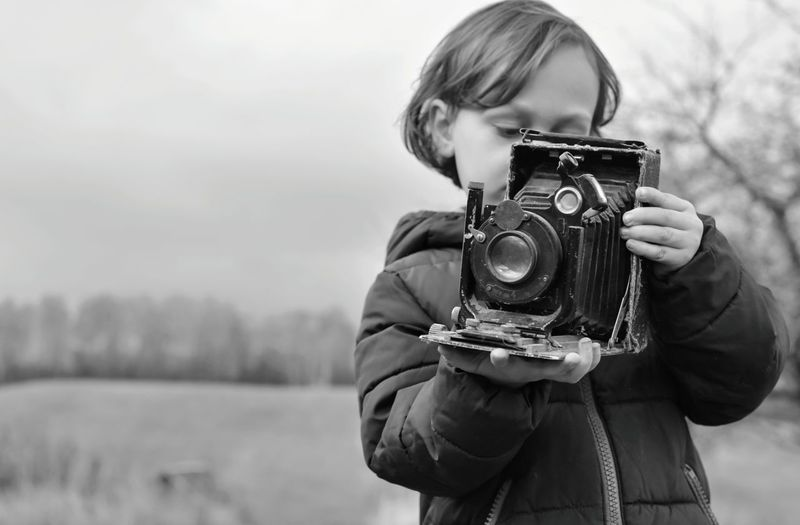 Girl holding vintage camera against sky
