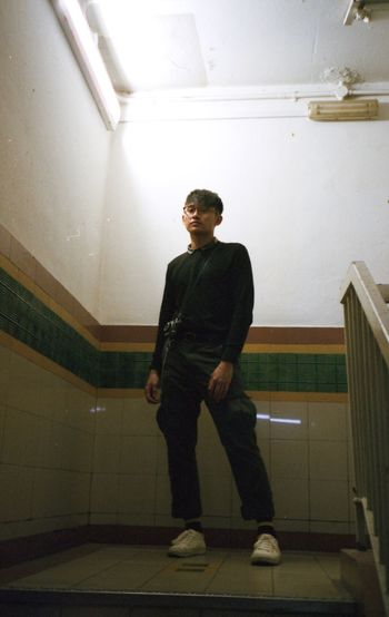 Full length portrait of young man standing on staircase in building