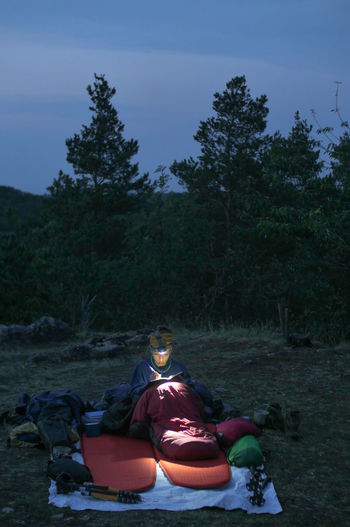 caucasian female hiker reading book/writing journal at night while wildcamping, strong light from headlamp Backpacking Camping Headlamp Hiking Light Reading Travel Trekking Woman Writing Adventure Beam Beauty In Nature Book Caucasian Clothing Day Evening Female Field Growth Hobby Journal Land Nature Night Non-urban Scene One Person Outdoors People person Plant Real People Relaxation Sitting Sky Sleeping Sleeping Bag Tranquility Tree