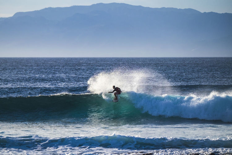 Silhouette Teenage Boy Surfing In Sea Against Mountains