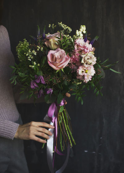 Midsection of woman holding rose bouquet